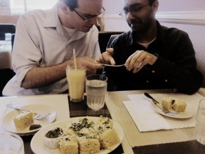Hull and Surendranath examine the inscription on a spoon at Bombay Cuisine.